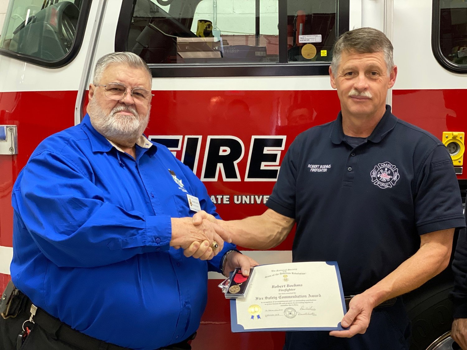 President Don Williams, left, of the Gadsden Chapter of the Sons of the American Revolution (SAR) and New Mexico State University firefighter Robert Boehms