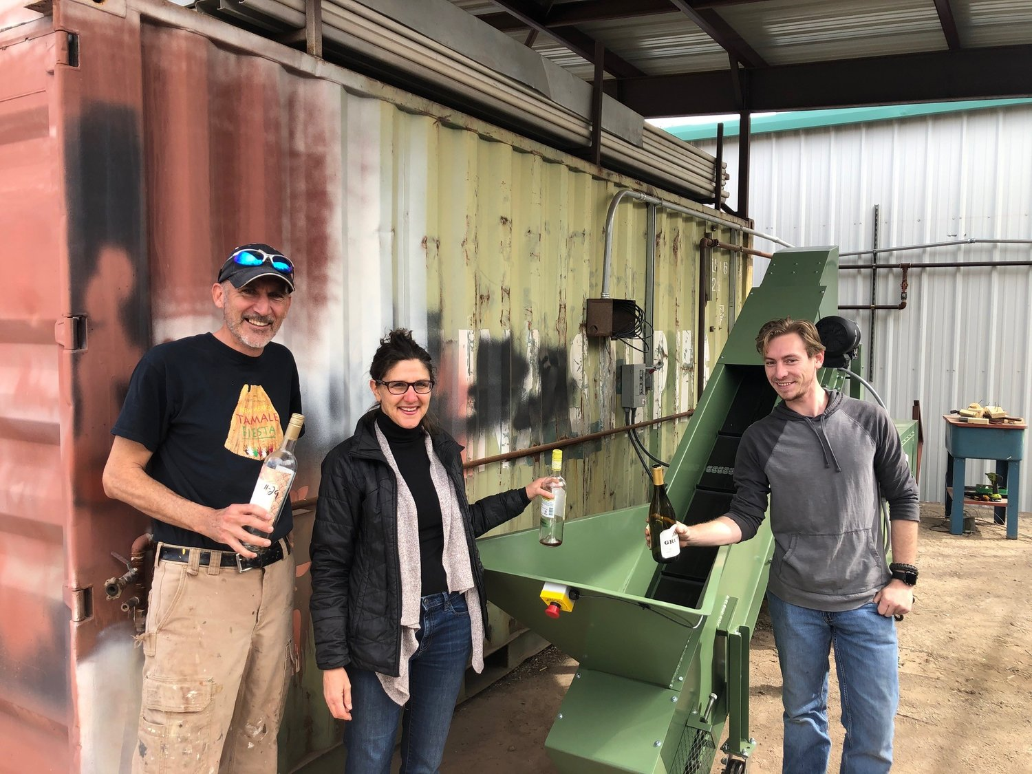 Trying out the new glass crusher in Silver City for the first time, organizers Chris Lemme, Alexandra Tager and Stephen Lindsey get ready to drop in their empty bottles.