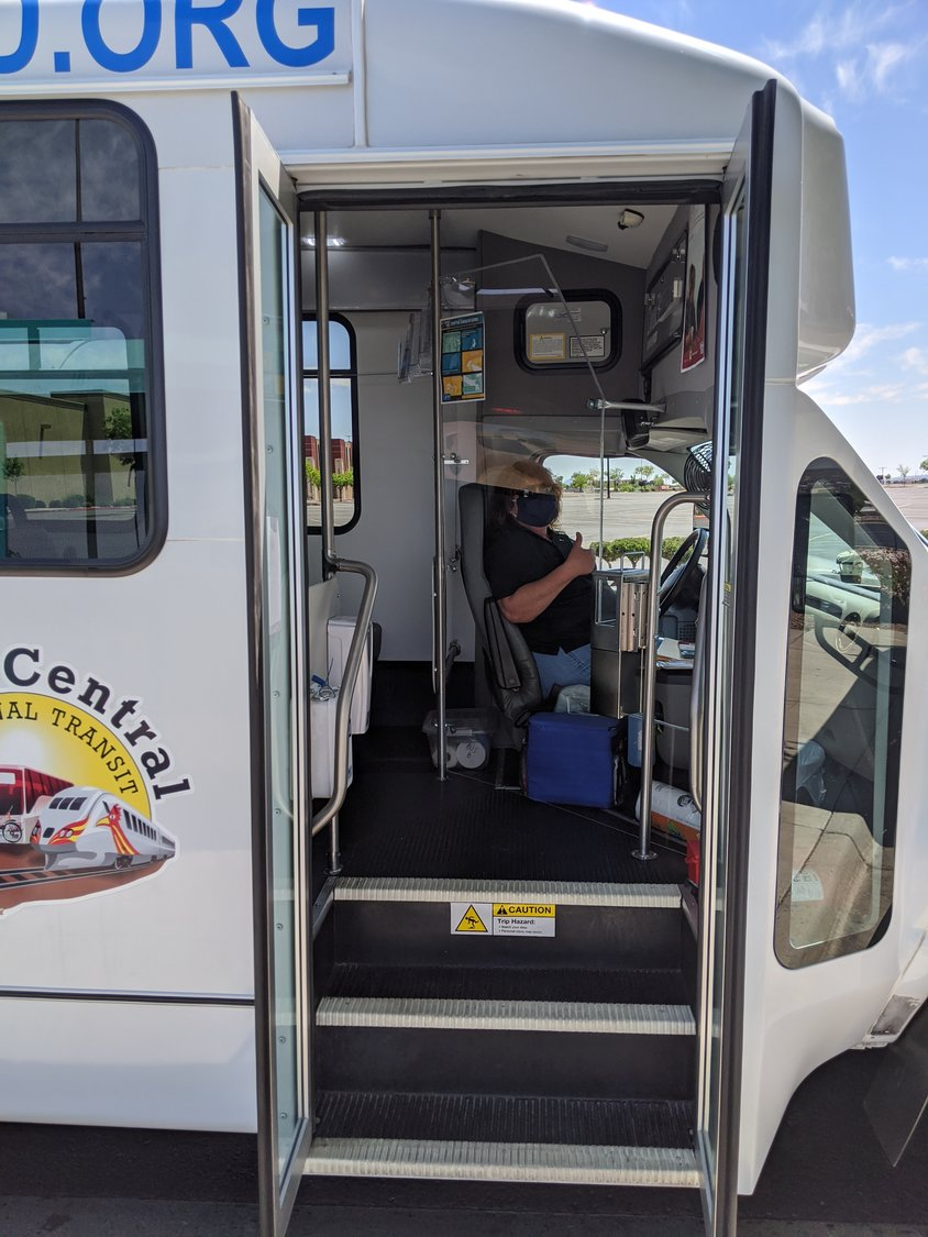 A masked South Central Regional Transit District driver sits behind a newly installed plexiglass shield designed to help prevent transmission of the COVID-19 virus