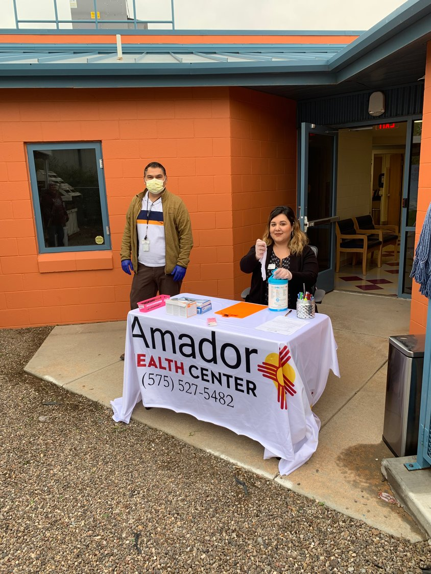 Amador Health Center Case Manager Jesus Ramirez and Front Office Intake Diana Salcedo work on the outdoor screening and triage table.