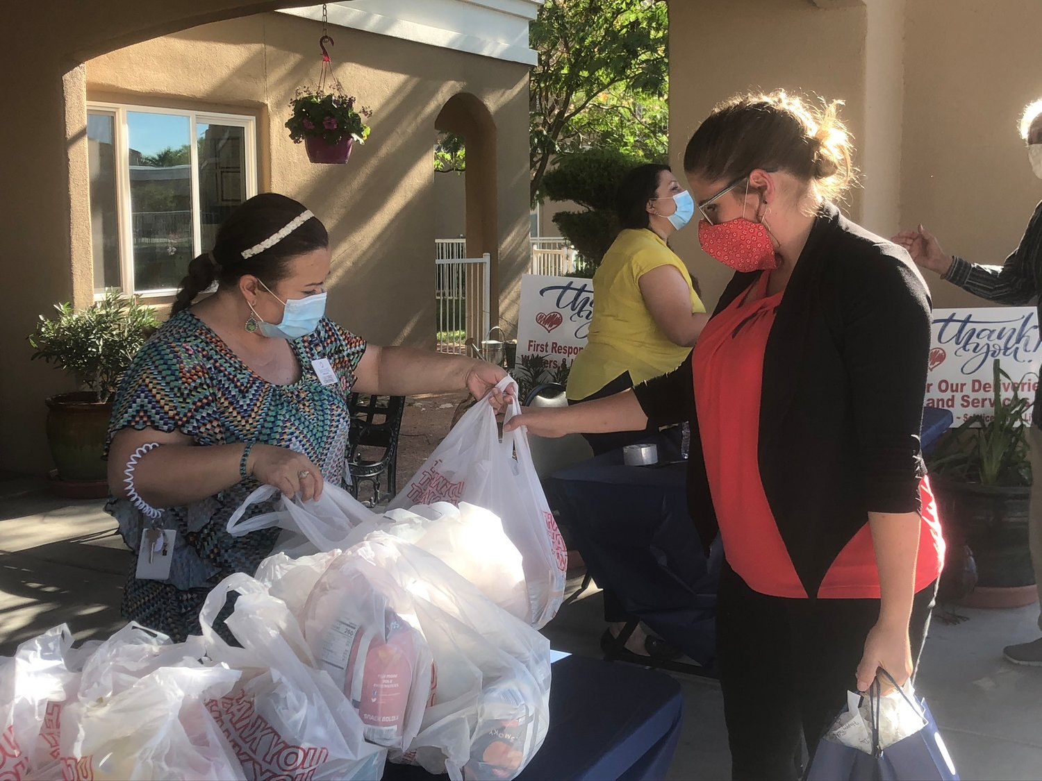 Emily Gomez, right, picks up a Father's Day picnic pack from Solstice Senior Living from concierge, Lily Cruz. At the next table, Renee Segura, director of sales and marketing for the facility hands out the beer to accompany the brats.