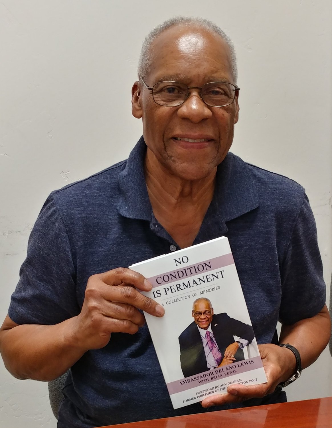 "Retired ambassador and author Delano Lewis with his book, ""No Condition Is Permanent: A Collection of Memories."""