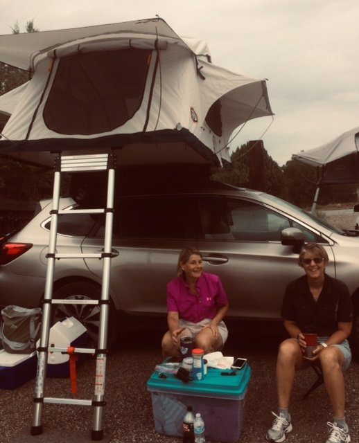 Laura and Louise enjoy their morning coffee after a good night's sleep in their rooftop tent.