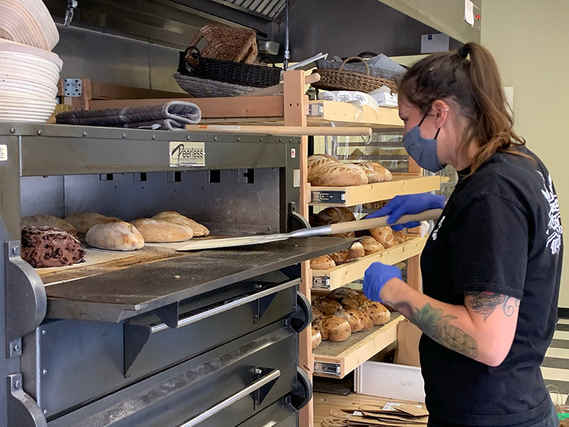 Kaleigh Jones shifts loaves around in the ovens at Kind Bread.