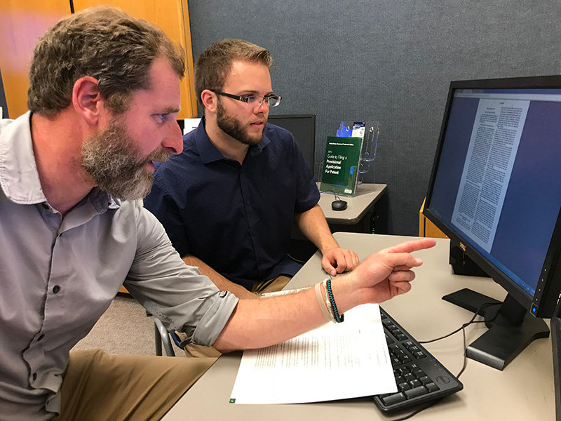 New Mexico State University business and government documents librarian and Patent and Trademark Resource Center representative David Irvin, left, helping NMSU biology doctorate student Alex Moon with patent research at the PTRC office in NMSU's Zuhl Library in 2018.