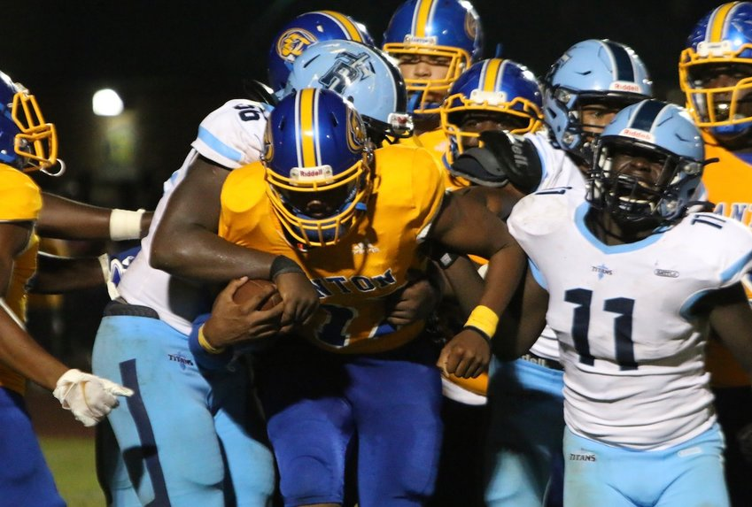 Canton's Tyquan Henderson tries to break away from Ridgeland tacklers Zion Nason (56) and Genada Byrd (11) Friday night in Canton.