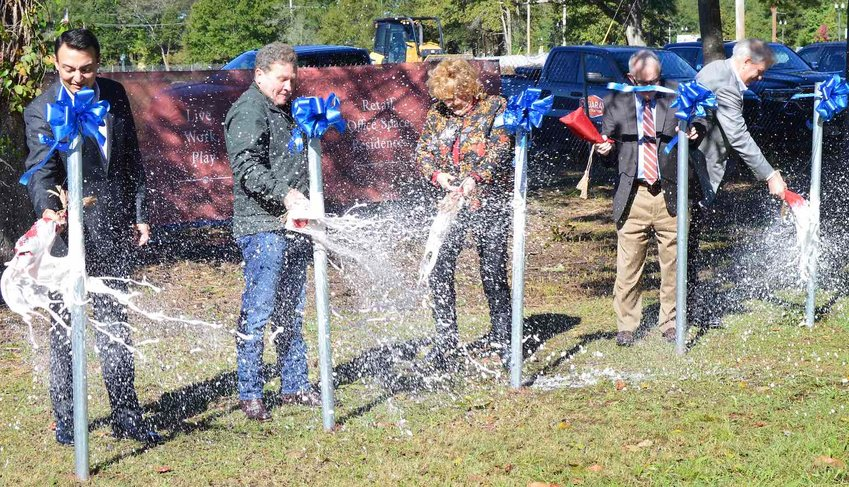 Officials break champagne bottles to celebrate a new $50 million development in Madison. Pictured are: Justin Suber, Madison the City Chamber of Commerce President; partner Dr. Michael Manning; Mayor Mary Hawkins Butler; partner Lee Stafford and partner Mark Castleberry.