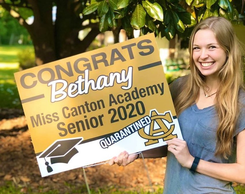 Canton Academy senior Bethany Biggers shows off a yard sign dropped off by school faculty.