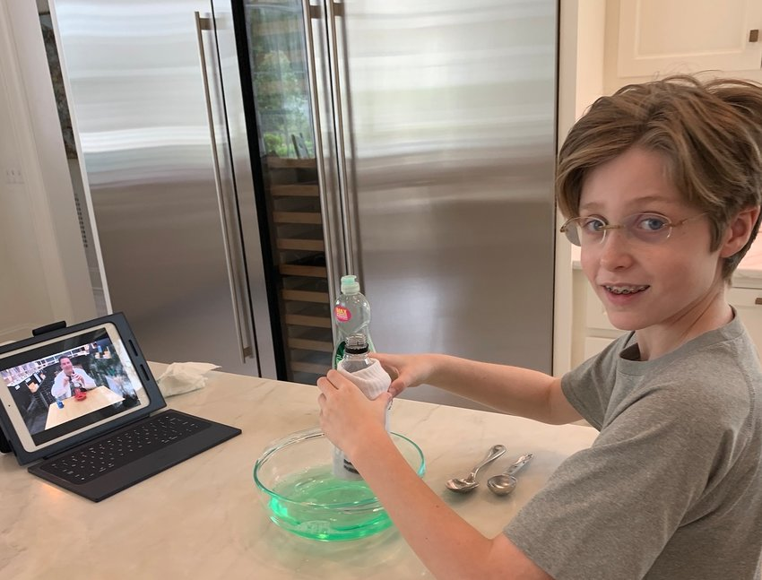 Peyton Smith of Ridgeland performs a science experiment while watching a video from Jackson Academy STEM teacher Cliff Powers. Teachers at JA are incorporating video lessons and uploading them to YouTube for students.