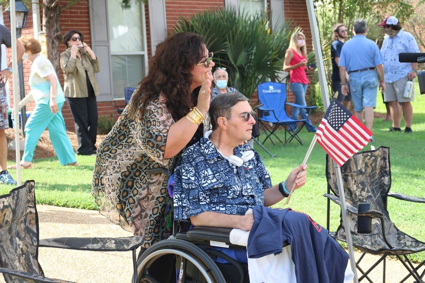 Madison Alderman-at-Large Warren Strain holds up an American flag as his wife Sandra Strain waves to people during a homecoming parade last Friday. Strain suffered a stroke on Dec. 23, 2019, and was recovering in Atlanta for several months.
