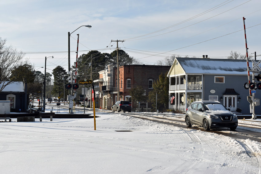 Cars make their way over the railroad tracks on Main Street in Historic Downtown Madison on Tuesday..(Scott Hawkins, The Madison County Journal)