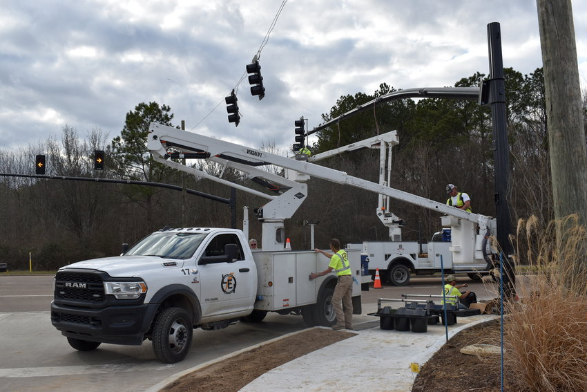Workers with Lewis Electric Inc. work Wednesday afternoon to install new permanent traffic signals at the Highland Colony Parkway entrance to Costco Wholesale Warehouse.