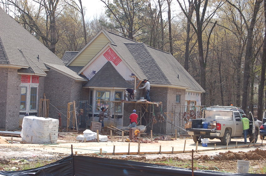Construction workers lay brick on a new home in Madison's Whittington development. An additional 52 home sites were approved by the city earlier this month. Once complete, the development off Welch Farms Road will feature a total of 152 homes.