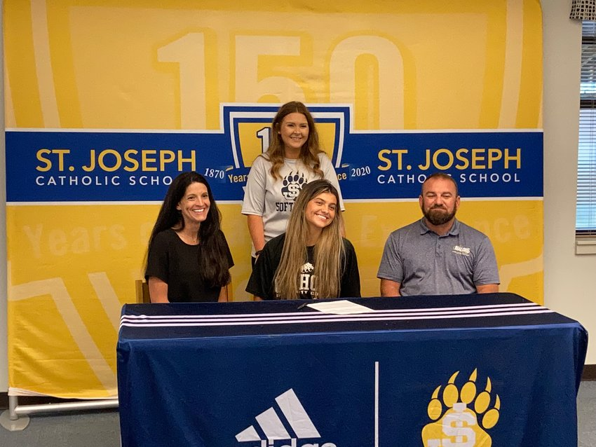 Pictured here are Edwards, center; Kelli Phillips, her mother, left; Dan Edwards, her father, right; and Danielle Poe, Bruin softball coach, standing behind Edwards.
