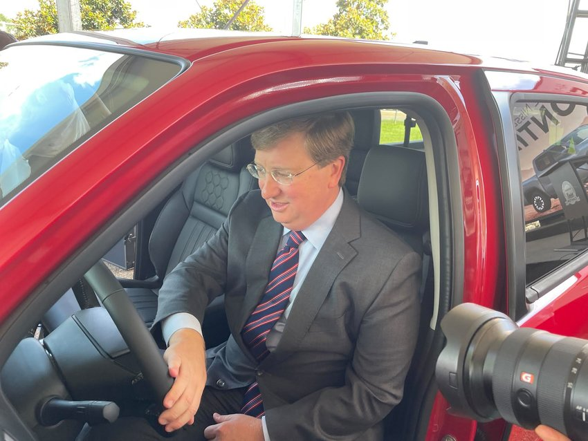Gov. Tate Reeves sits behind the wheel of a brand new 2022 Nissan Frontier truck that was manufactured at the Canton plant. Automobile executives and business leaders announced the truck would be made exclusively in Madison County.