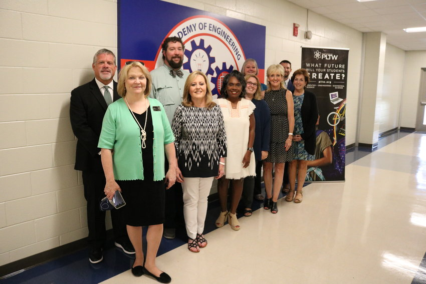 Pictured here before the implementation of required masks in Madison County Schools buildings, are PLTW Director of School Engagement Sherry Worsham, Madison Central Principal Sean Brewer, engineering teacher Cam Ogletree, aerospace engineering teacher David Wilbanks, Superintendent Charlotte Seals, MCHS Academy of Engineering Director Michelle Robinson, biomedical interventions teacher Betsy Sullivan, Assistant Superintendent Edith Mitchell, Assistant Principal Mary Edwards, and MCS Director of Career and Technical Education and Career Academies Blaise King.