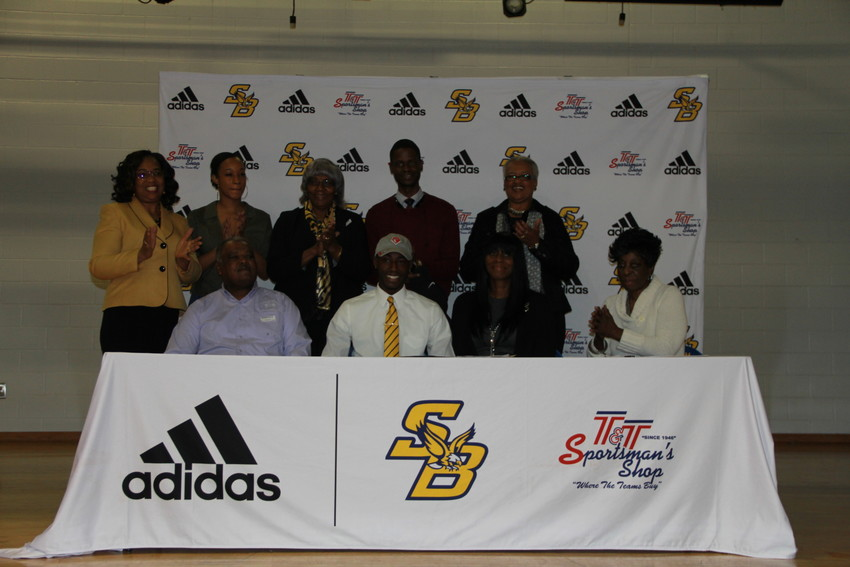 Flanked by proud parents and surrounded by family, Amonte Brown signs to play with Newberry College.