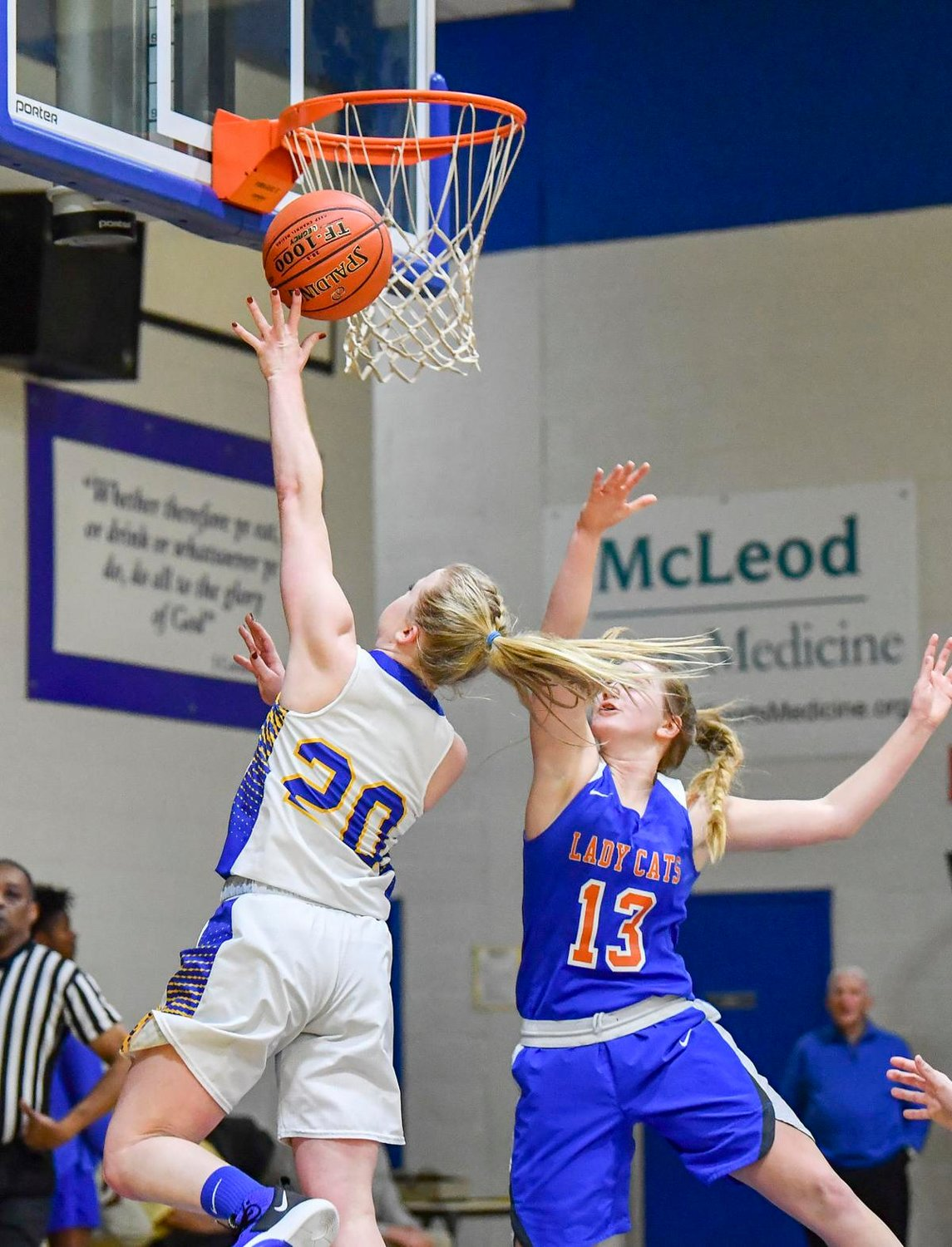 Florence Christian School's Kylie Stewart completing a layup with Katherine Burns contesting it.