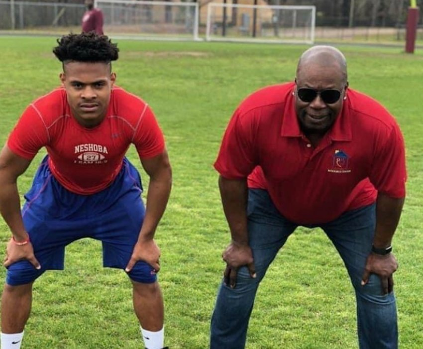 Neshoba Central running back Jarquez Hunter on the field with legend Marcus Dupree.