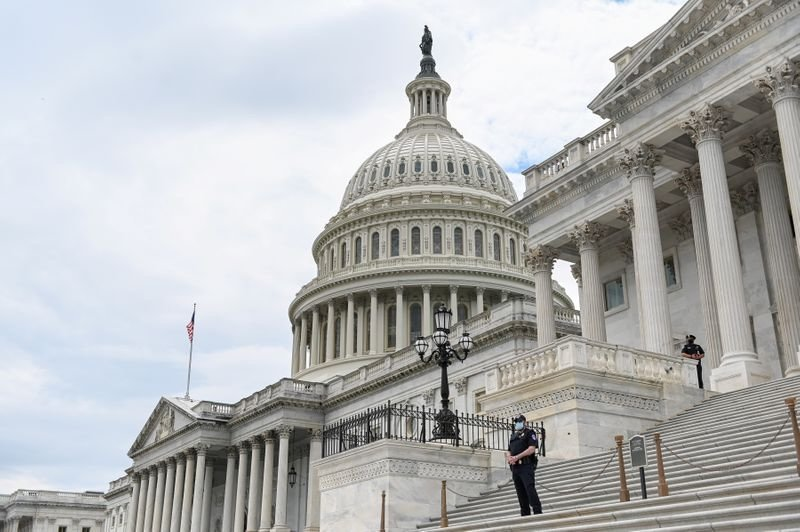 FILE PHOTO: Police officers wearing face masks guard the U.S. Capitol Building in Washington, U.S., May 14, 2020. REUTERS/Erin Scott