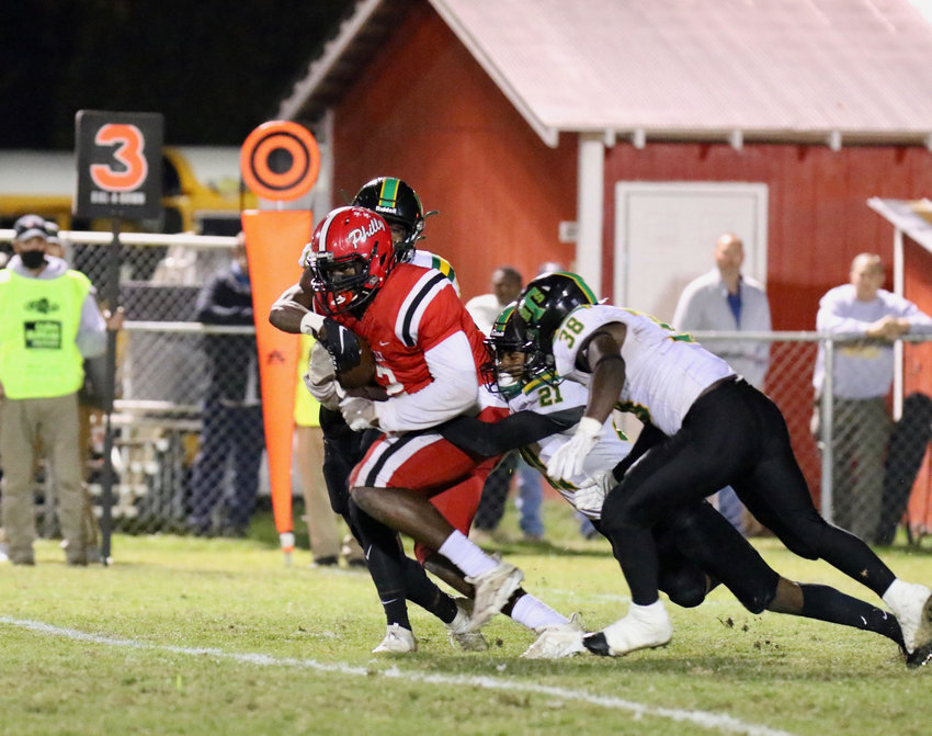 Jatarian Hudson (2) drags some Taylorsville defenders for a Tornadoes first down.