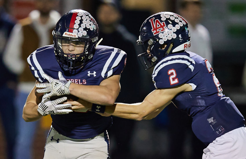 Leake Academy quarterback Rhett Atkinson hands the ball off to Canon Parks in the state championship game.
