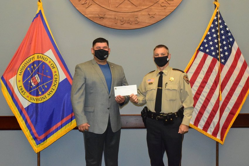 Mississippi Band of Choctaw Indians Tribal Chief Cyrus Ben presents Neshoba County Sheriff Eric Clark with a donation that will be used to purchase TASERs.