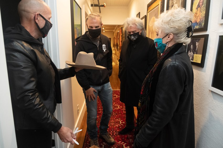 Doug Hudson, left, gathers with John Peets, Marty Stuart and his wife Connie Smith in Hudson's Busy Bee Suites apartment as they look at a hat that belonged to Hank Williams Sr., all part of Stuart's Congress of Country Music that is being developed here.