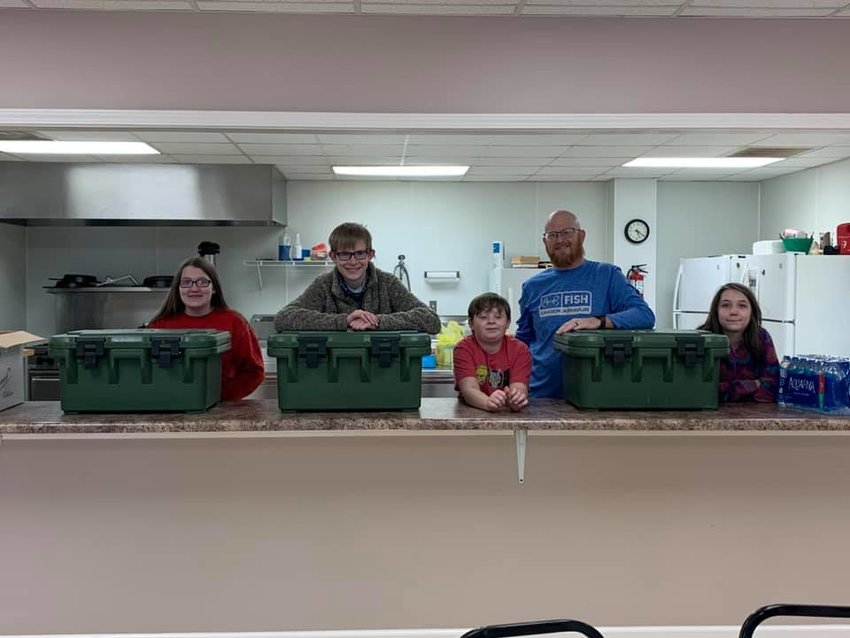 Ivie Savell, Eli Sharp, Evan Sharp, the Rev. Eric Sharp and Chloe Savell prepare to hand out food and water at New Bethel Baptist Church.