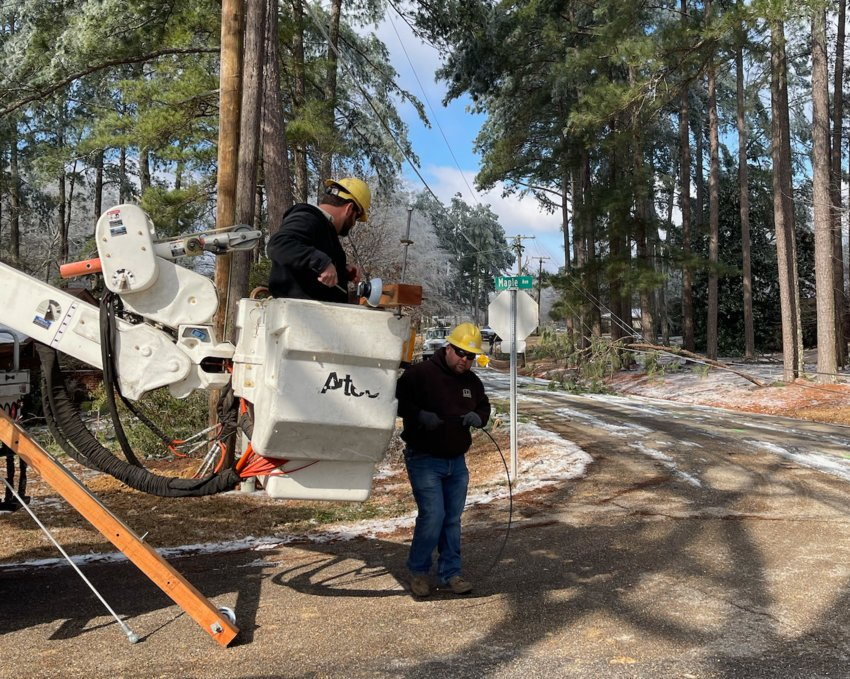 A crew works to restore power on Maple Avenue in Woodland Hills following winter storms that hit Mississippi in February. Ice accumulation on power lines and trees caused severe power outages throughout most of Neshoba County.
