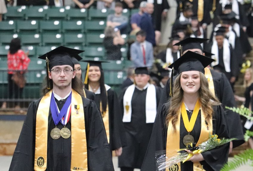 Union High School Valedictorian Greg Palculict, left, and Salutatorian Autumn Payne, right, lead the student procession on May 13 at the Neshoba County Coliseum.