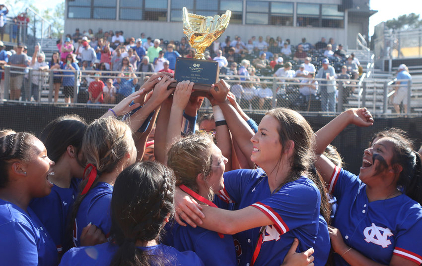 The Neshoba Central Lady Rockets hold up the Class 5A State Softball Championship trophy after beating Moss Point's East Central Hornets on Friday for their eighth straight title.