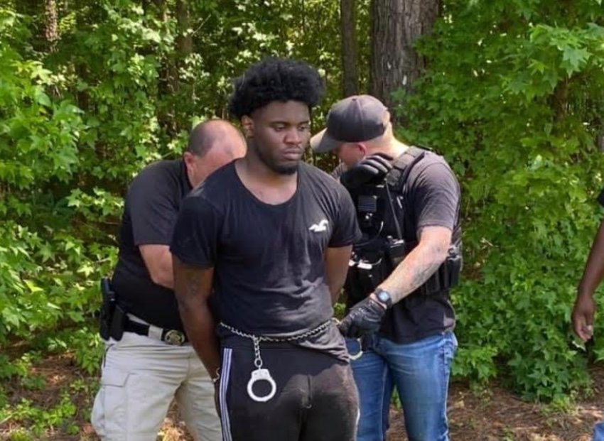Law enforcement officials take Demarquese Gibson, 20, of Grenada into custody in Louisville on Wednesday. Officials said Gibson, who was being transported to the Winston County Jail on a grand larceny charge escaped on Tuesday.