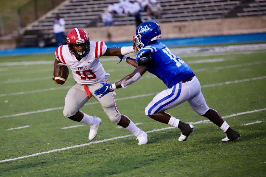 Philadelphia quarterback Marcus Beamon tries to elude a Meridian High defender Friday night.