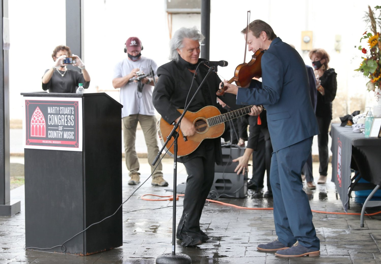 Neshoba County's own Marty Stuart jams out with bluegrass musician Stuart Duncan, right, last Wednesday during a topping off ceremony for the Marty Stuart Congress of Country Music downtown. The event was curtailed by the coronavirus pandemic.
