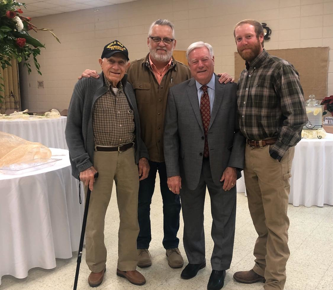 World War II veteran Glen Belenchia, left, stands with his family members. Pictured from left to right: Glen Belenchia, Mark Belenchia, Dr. Russell Belenchia, and Rusty Belenchia.