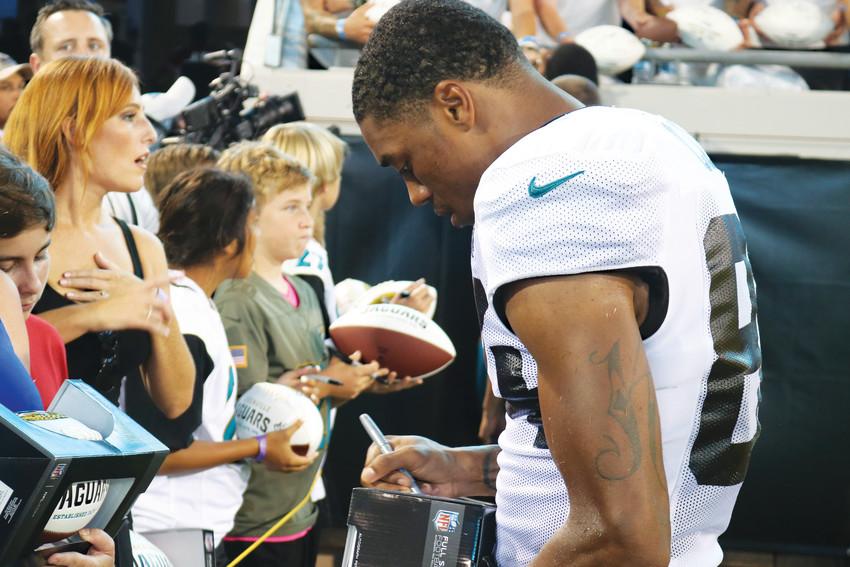 Jaguars wide receiver Keelan Cole signs autographs for fans.