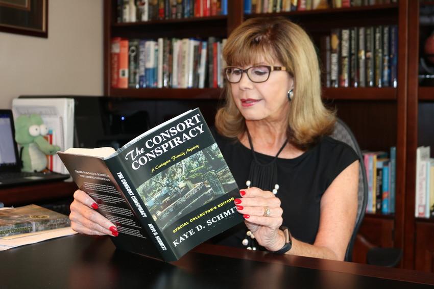 "Schmitz flips through her first novel, ""The Consort Conspiracy, A Covington Family Mystery."""