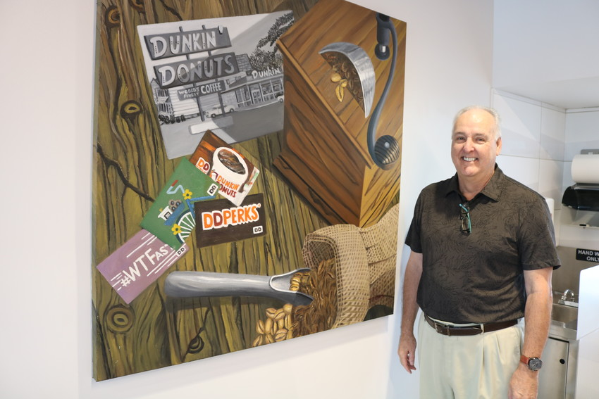 Ponte Vedra artist Bill Adams stands next to a painting he produced for the first next generation Dunkin' Donuts store in Florida, located in St. Augustine.
