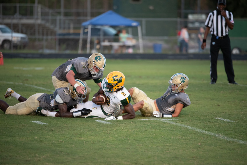 Nease defenders, including Dequan Thompson (25) and Zach Harmon (54), tackle White running back Isaiah Flowers during last Friday's game.