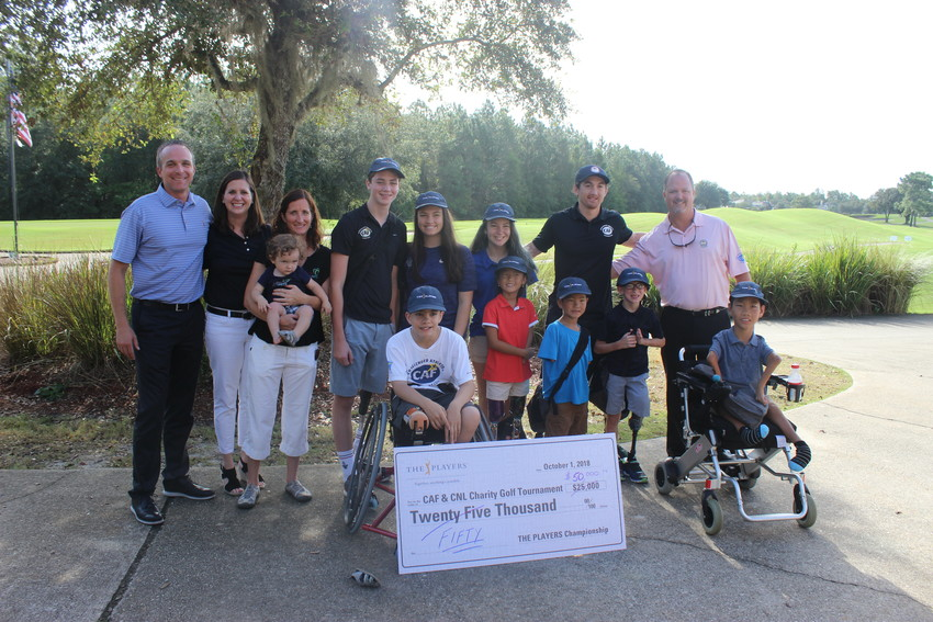 THE PLAYERS Championship Executive Director Jared Rice (left) presents the Challenged Athletes Foundation (CAF) and Camp No Limits (CNL) Golf Tournament and friends with a check donation for $50,000 Oct. 1 at the Golf Club at South Hampton in St. Augustine.