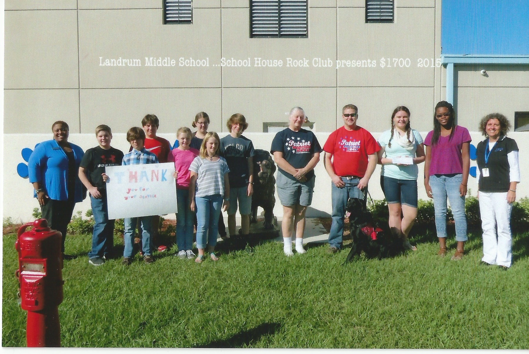 From Pictured from left to right are: Principal Jewel Johnson, Jonathan Southerland, Harry O'Connor, Isabella DiStefano, Phoebe Collins, Kendall Welling, Max McBride, Volunteer for Patriot service Dogs Susan Bolton, Veteran Chris Smith, Service Dog Georgia, club presidents Brielle Kelley and Alyssa Bacchus, and sponsor Laurie Stanton.