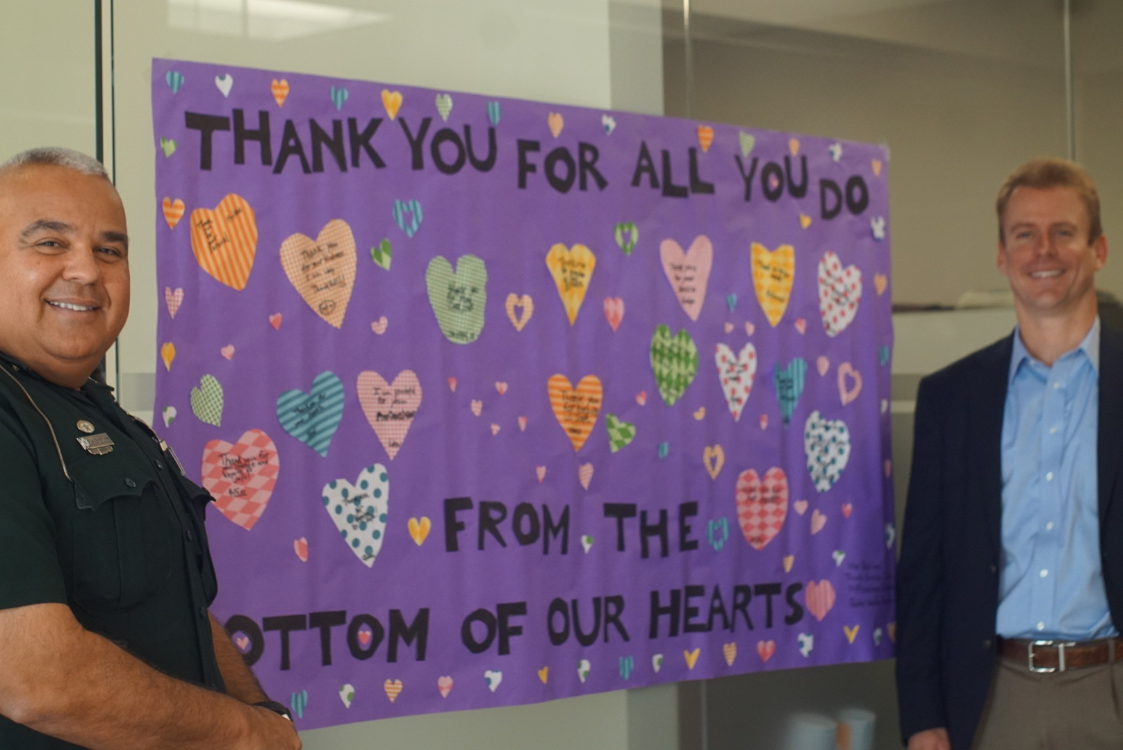 Managing Broker Kevin Waugaman (right) poses with Deputy Refael Fuentes in front of Mrs. Beliles' third graders' handmade poster. Mrs. Mary Beliles' third grade class at PVPV/Rawlings Elementary's specially prepared a poster of handwritten messages on cutout hearts thanking Ponte Vedra's first responders for their work keeping the area safe.