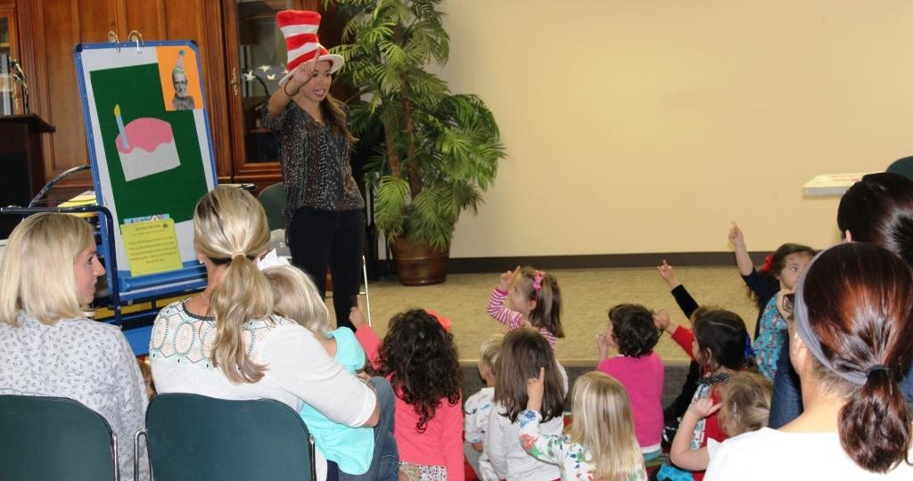 Youth Services Intern, Ms. Sherrie, leads at Dr. Seuss fingerplay with the Pre-K Storytime Class