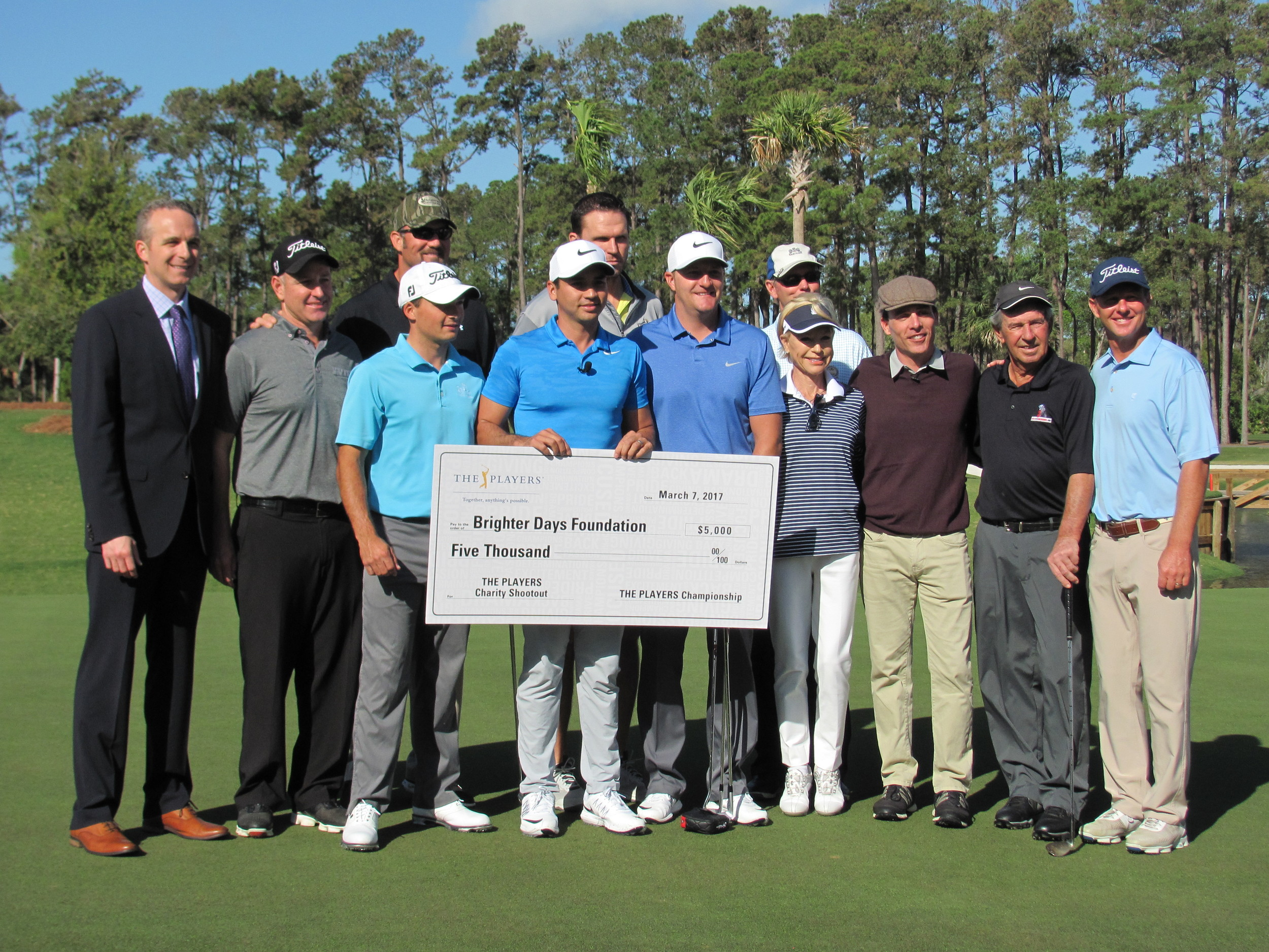THE PLAYERS present Jason Day's charity with a $5,000 check, and Jason Day donates $5,000 to each of the event's participating charities in turn.