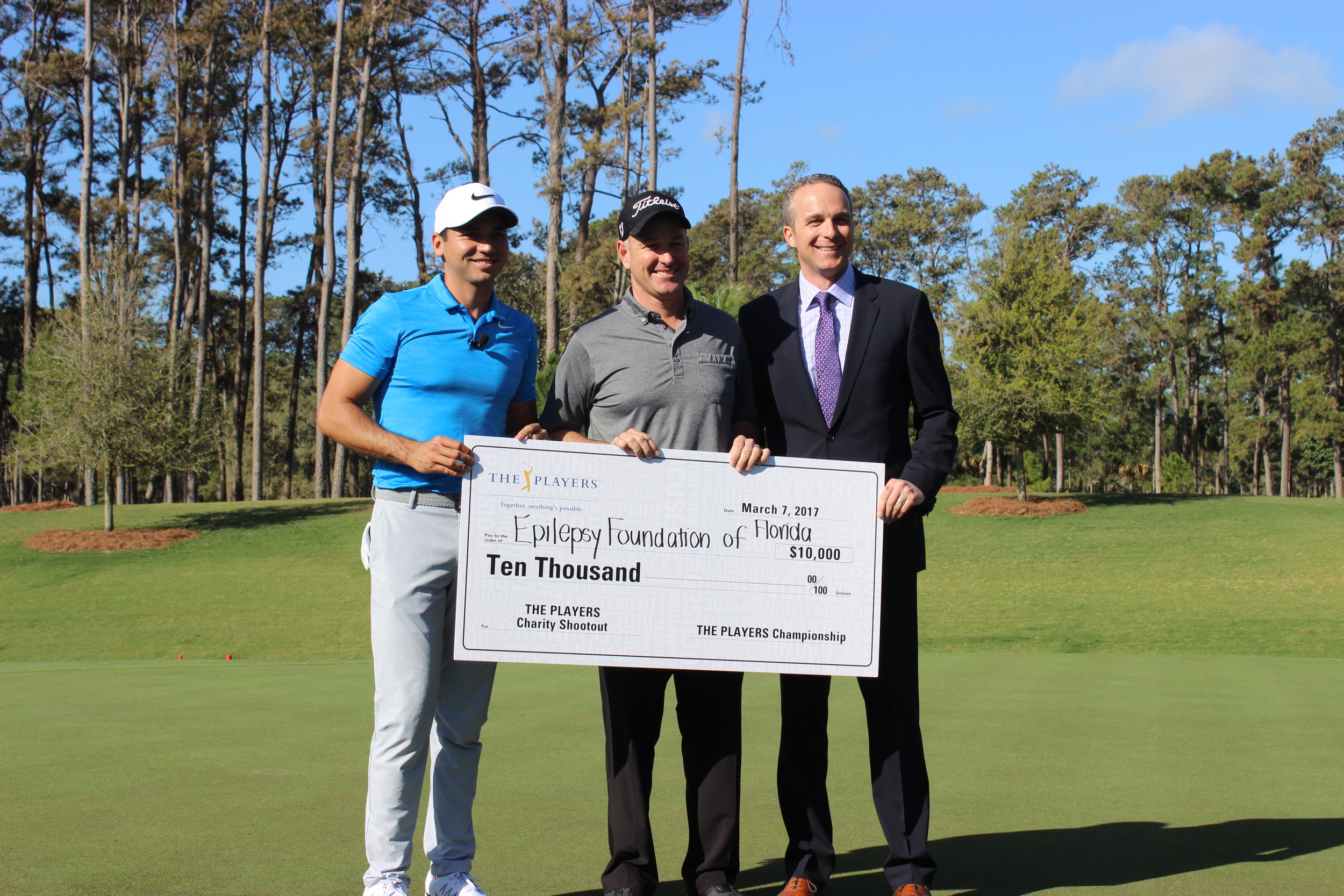 PGA Tour player Jason Day (left) and THE PLAYERS Championship Executive Director Jared Rice (right) present former PGA Tour player Jeff Klauk (center) with a $10,000 donation for Epilepsy Foundation of Florida after Klauk won the Charity Challenge.