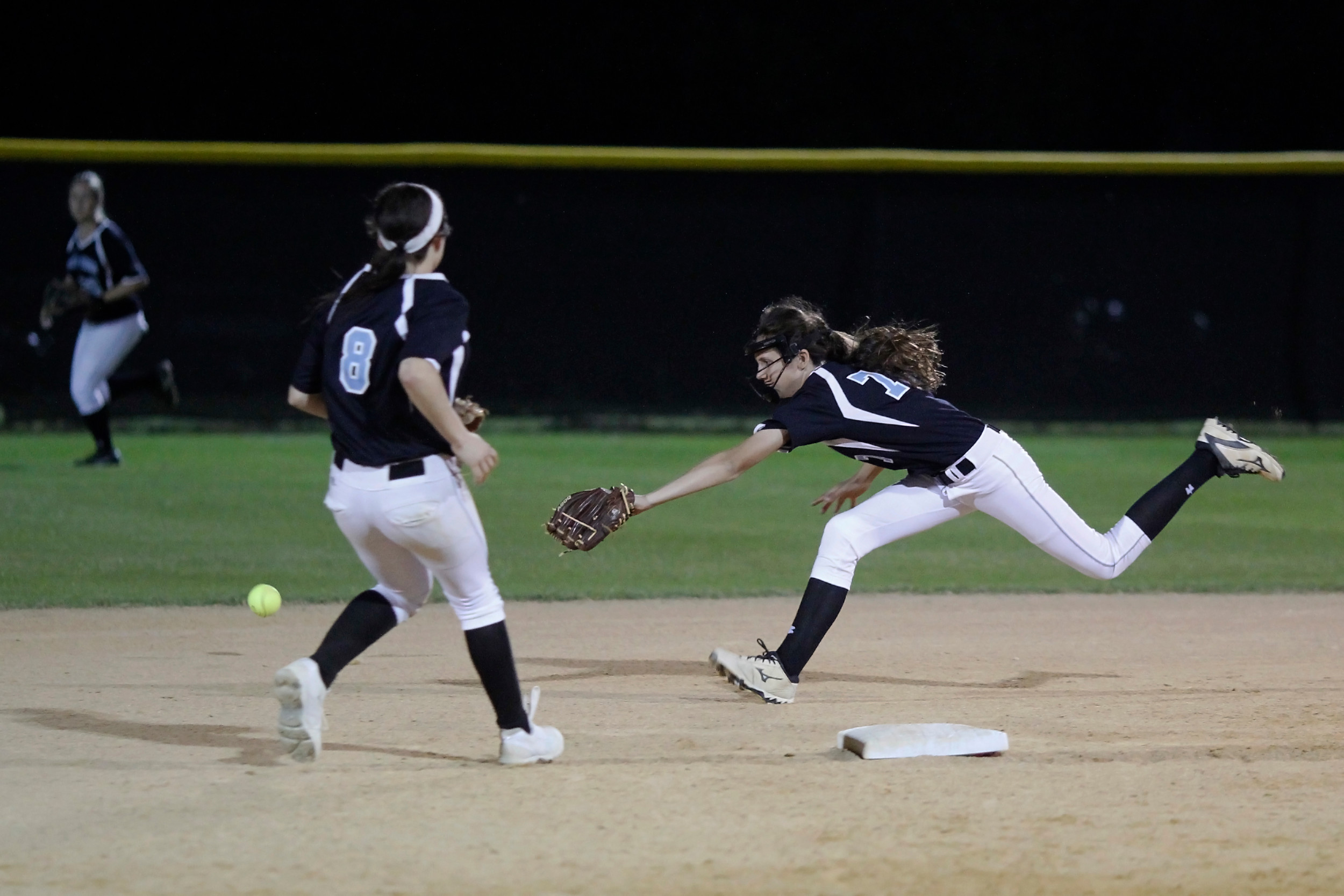 #77 Catherine Beaton makes a futile lunging attempt to field a Trinity base hit.