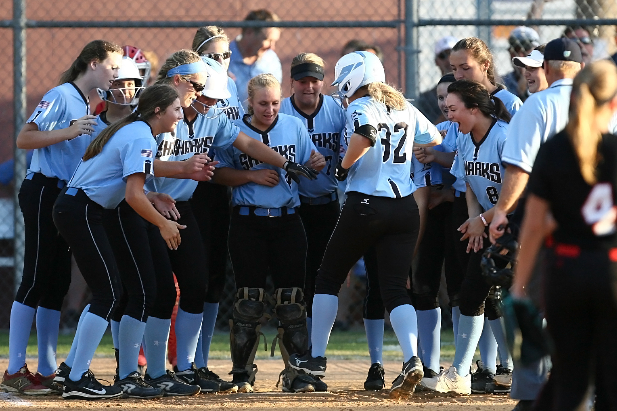 Sharks welcome #32 Farley Callaghan at the plate after her two-run home run.