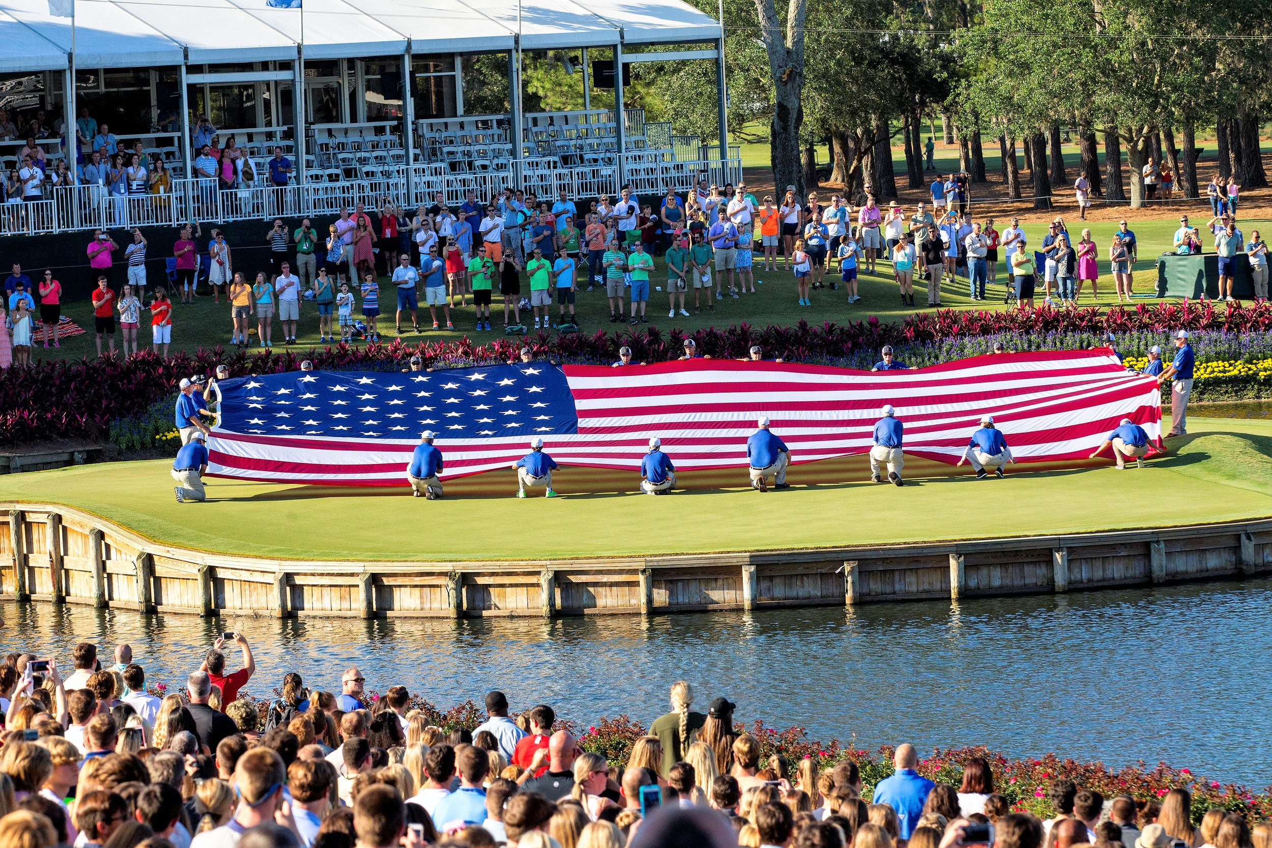 A giant American flag is unfurled on the iconic TPC Sawgrass island green.