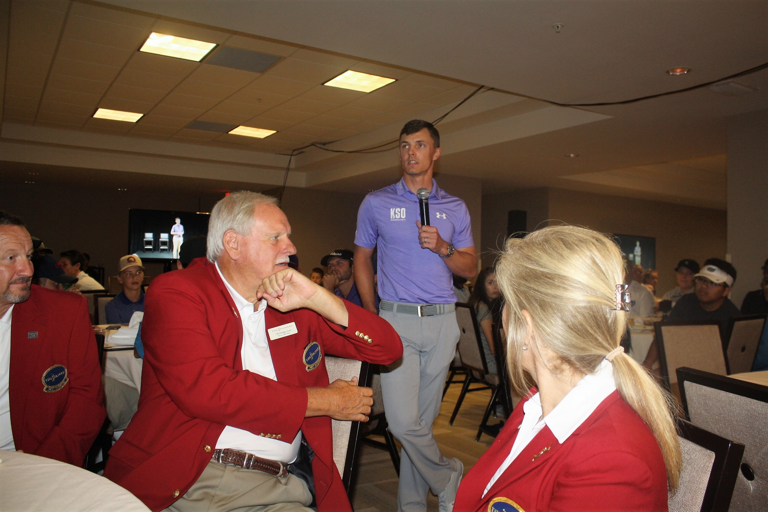 Members of THE PLAYERS Championship Red Coats volunteer leadership listen as Blayne Barber describes his experiences with FCA Golf.